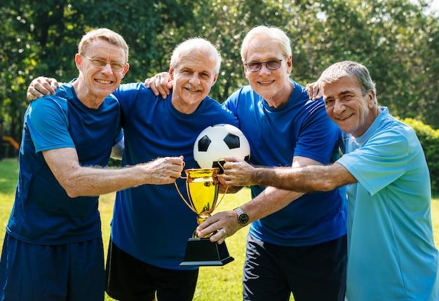 カップを獲得した成熟したサッカー選手のチーム