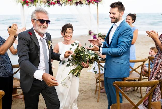 ビーチで結婚する若々しい成熟したカップル