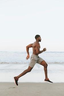 早朝にビーチで走っている男に合う