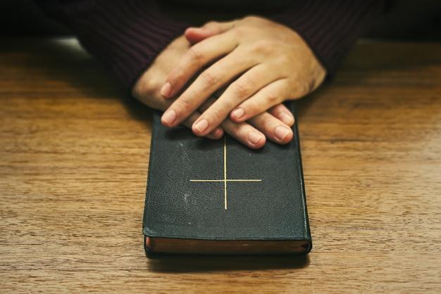 木製のテーブルの上の聖書の上の手