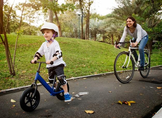 Мать и сын едут на велосипеде в парке