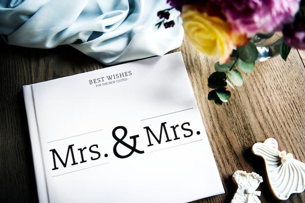 白いレズ結婚式のゲストブックは、木製のテーブルに置か