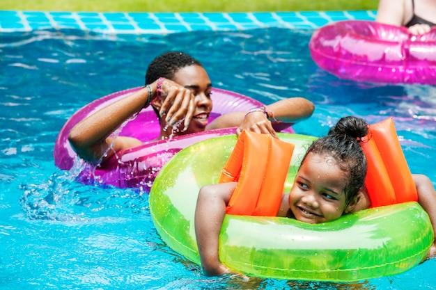 Макрофотография черная мать и дочь, наслаждаясь бассейн с надувные трубы