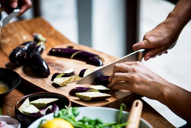 ナイフ刈りナスと手のクローズアップ
