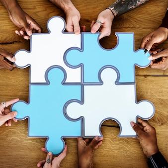 人々ジグソーパズル一緒にパートナーシップのチームワーク