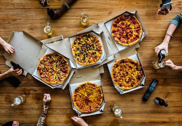 人々の手はピザのスライスをつかむ