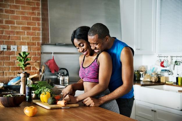 黒のカップルは、キッチンで健康的な料理を調理する
