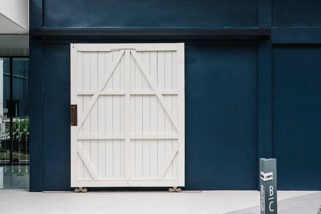 青い建物の壁に木製の白いドア