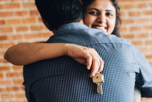 彼らの新しい家に鍵を抱えている陽気なカップル