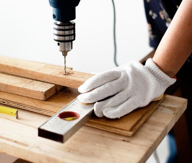 木製の厚板を掘削する女性