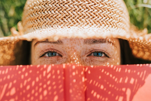 赤い本で彼女の顔を覆う女性のクローズアップ