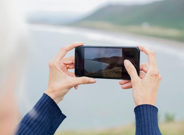 海の写真を撮っている高齢の女性