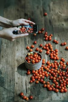 Женщина фотографирует красные помидоры черри
