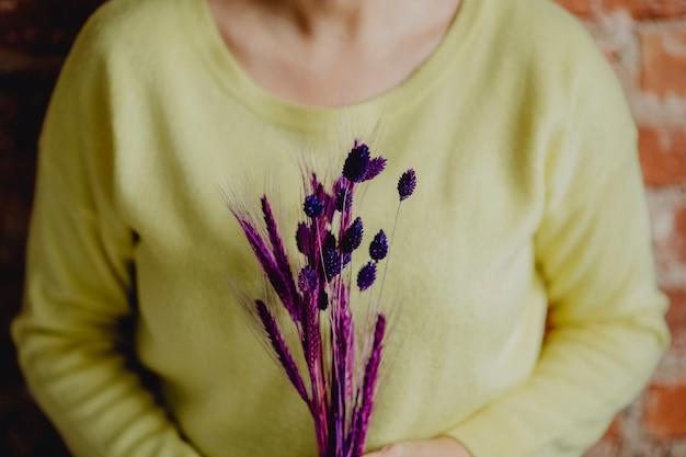 紫色の染め小麦の束を持っている女性