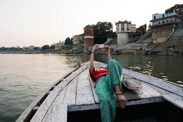 Западная женщина лежит на лодке, принимая селфи в варанаси