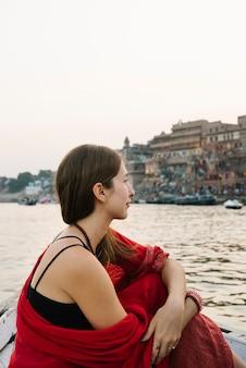 Западная женщина на лодке исследует реку ганг