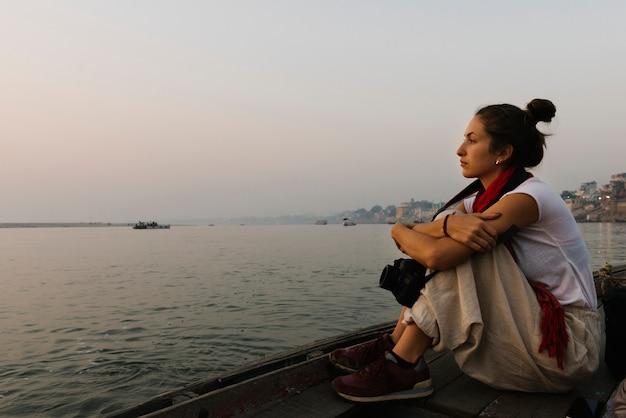 Фотограф сидит на лодке по реке ганг