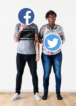 Люди держат две иконки социальных сетей