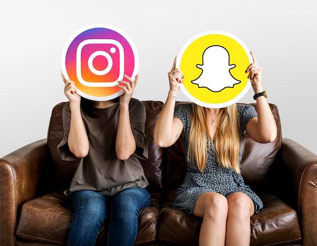 ソーシャルメディアのアイコンを持っている女性