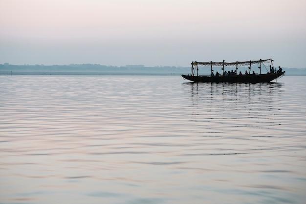 Деревянная лодка, плывущая по реке ганг в варанаси, индия