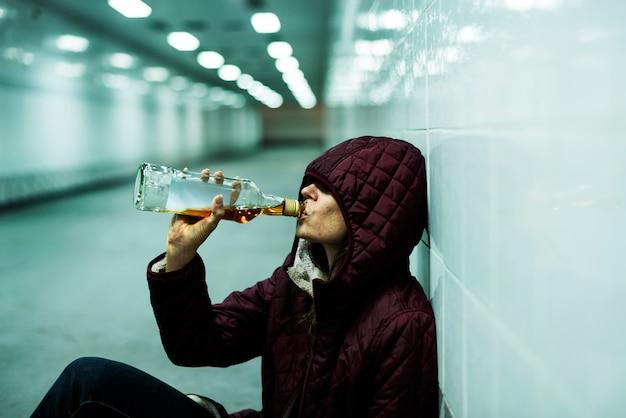Бездомный алкоголик пьет алкоголь, сидя на полу
