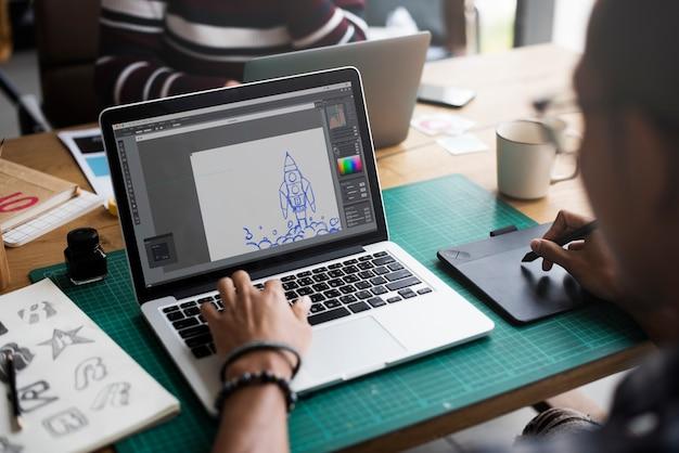 ノートパソコンとマウスパッドを操作するグラフィックデザイナー