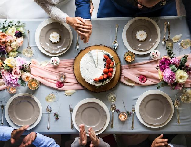 新婚カップルの手一緒にケーキを切る空撮