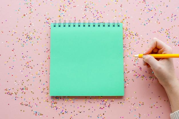 空白のノートブックと紙吹雪を持つペン