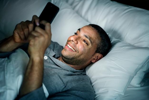 Человек с помощью телефона на кровати