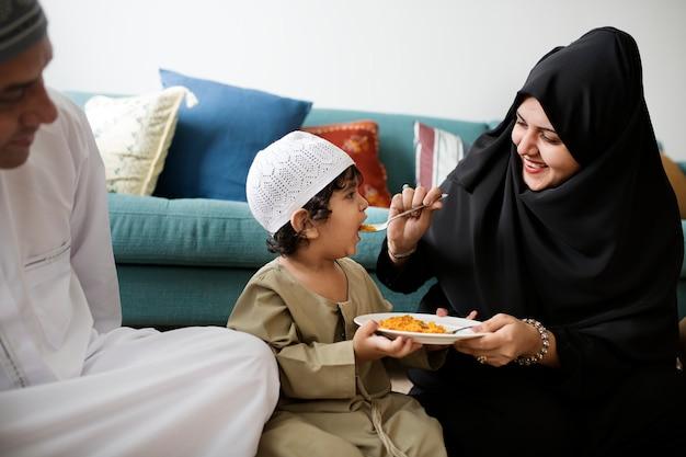 床で夕食を食べているイスラム教徒の家族