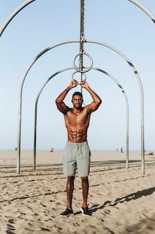 ぴったりの男性、ビーチでのエクササイズ