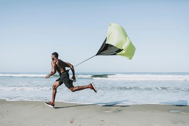 ビーチで実行中のパラシュートを持つ男に合います