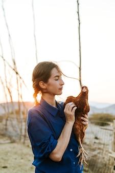 茶色の鶏を持つ若い女