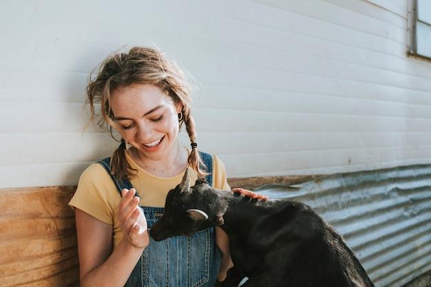 黒赤ちゃんヤギと遊んで幸せな若い女