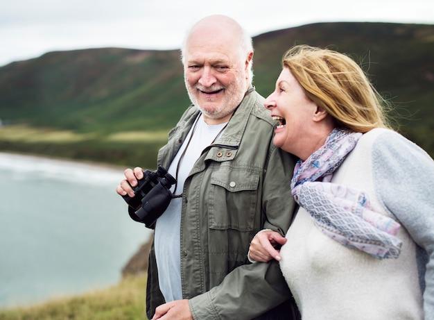 Счастливая пара старших, наслаждаясь с биноклем