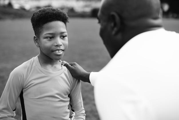 ゴールキーパーに助言するフットボールのコーチ