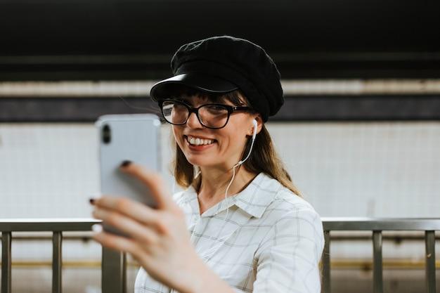 地下鉄のプラットフォームでビデオ通話を持つ陽気な女性