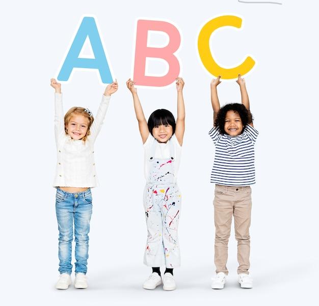 Разнообразные счастливые дети изучают азбуку