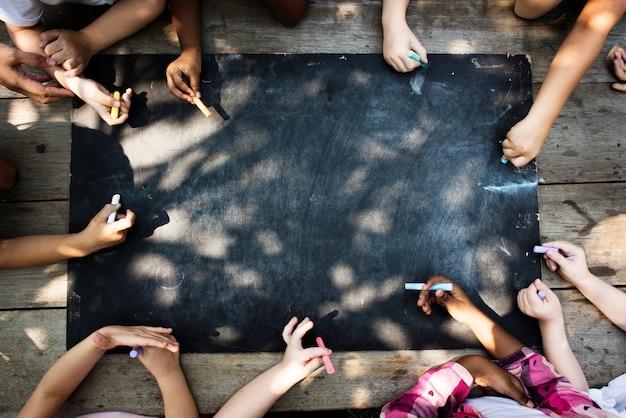 Разнообразная группа детей, рисование на доске