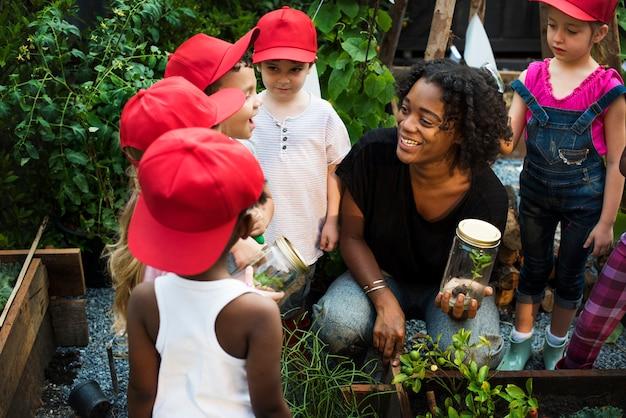 農場で環境を学ぶ多様な子供たちのグループ