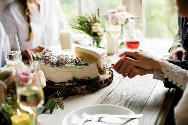 一緒にウェディングケーキを切る新郎新婦