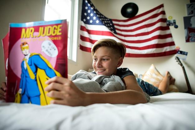 ベッドの上の読書漫画横になっている若い白人少年