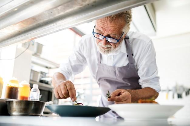 調理済みの料理を飾るキッチンスタッフ