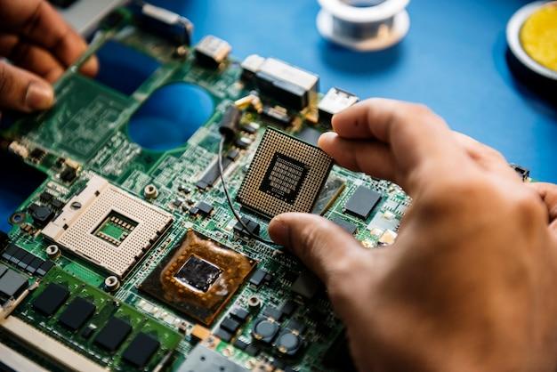 コンピューターのマイクロプロセッサを持つ手のクローズアップ