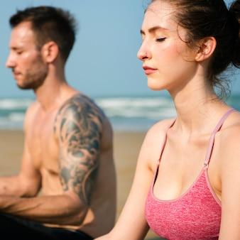 Пара занимается йогой на пляже