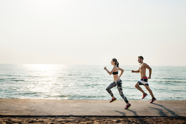 一緒にビーチを走る健康的な若いカップル