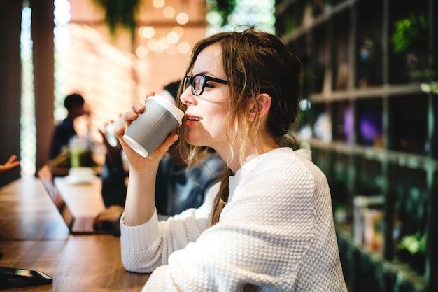 一杯のコーヒーを飲んでいる金髪の女性