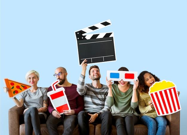 映画の絵文字を保持している多様な友達のグループ