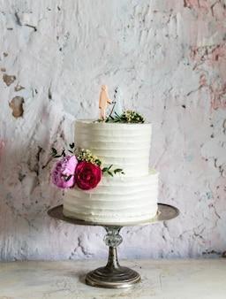 新郎新婦のトッパーと白のウェディングケーキ