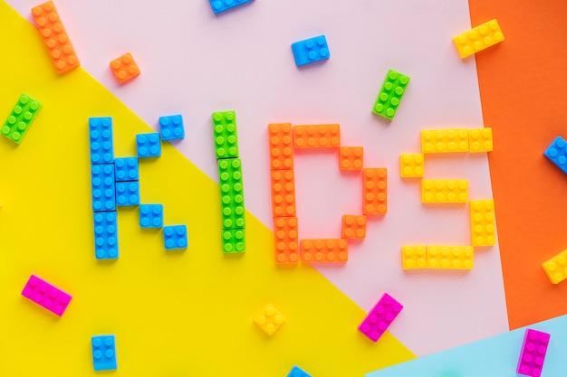 子供たちはプラスチック製のブロックの背景を持つ単語のスペル